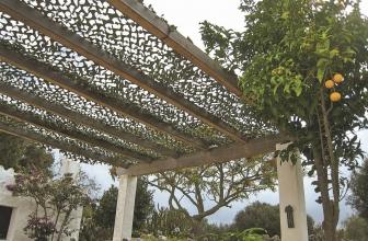 Une pergola réalisée avec un filet de camouflage et des palettes